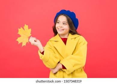 Hello september. Little girl welcome autumn season. Kid girl cute face hold maple leaf. Child with autumn yellow leaf. Autumn is here. Small girl wear fall outfit on red background. Enjoy season.