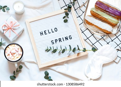 Hello spring concept flat lay on the white blanket. Breakfast in the bed top view card with text