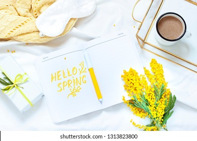 Hello spring flat lay composition with mimosa flowers, a cup of coffee and a gift. Concept womans or mothers day top view.