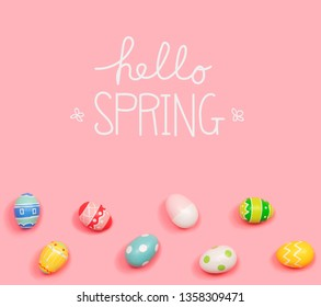 Hello spring message with Easter eggs on a pink background