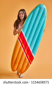Hello, summer! Attractive young woman in swimwear isolated on orange background. Happy girl in pink sunglasses is posing with inflatable surfboard.