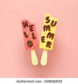 Hello Summer chocolate text and two ice creams with sprinkles on pink pastel background.