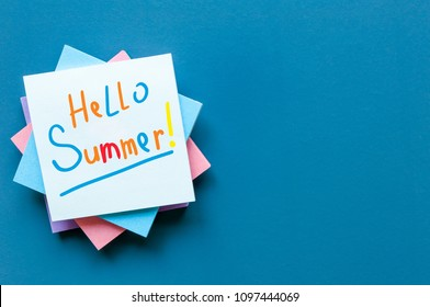Hello Summer - inscription of many colored letters at notes on blue background. First summer day, Calendar concept. With copy space for text