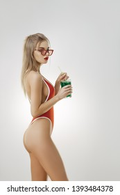 Hello, summer. Portrait of a stunning lady with perfect figure in a red sexy swimsuit and retro sunglasses holding sweet tasty cocktail isolated on bright copy space background in studio. Gorgeous