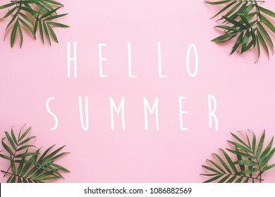 Hello Summer text on fresh palm leaves border on pink background with space for text. stylish summer vacation flat lay. hello holidays