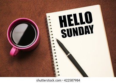 Hello Sunday - text on notebook with a pen and cup of coffee