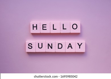 Hello sunday words wooden cubes on a pink background