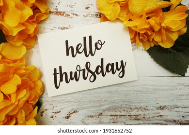 Hello Thursday Card with Blooming flower on wooden background