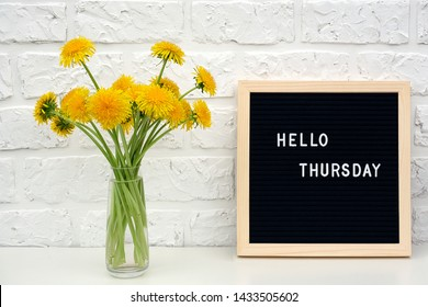 Hello Thursday words on black letter board and bouquet of yellow dandelions flowers on table against white brick wall. Concept Happy Thursday. Template for postcard.