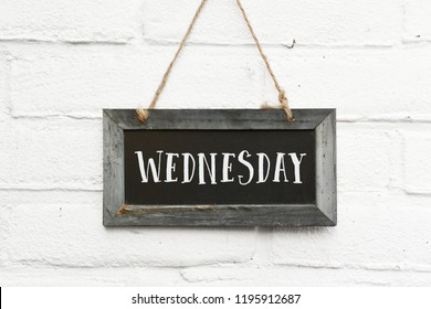 Hello wednesday text on hanging board white brick outdoor wall