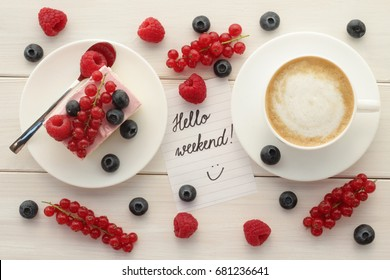 Hello weekend, summertime, morning coffee, coffee break concept. Hello Weekend words on paper, cup of coffee, cake with fresh summer berries on white wooden table.  Top view, flat lay.