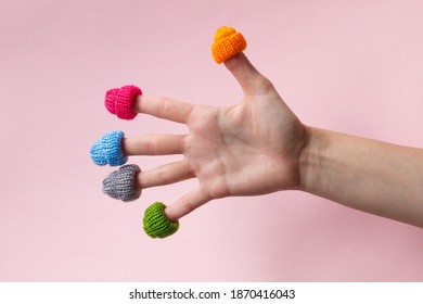 hello winter, female hand with fingers wearing warm colorful knitted hats isolated on pink