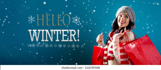 Hello winter message with young woman holding shopping bags