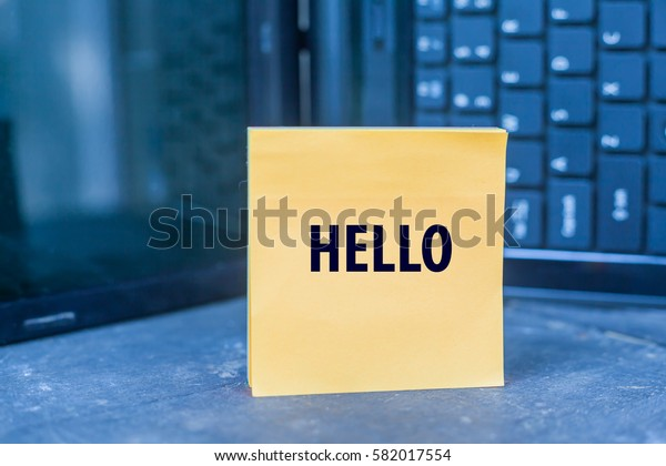 HELLO word on paper note on wooden table over blurry laptop as a background