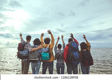 Hello world. Portrait of friends greeting seaside holding their hands up