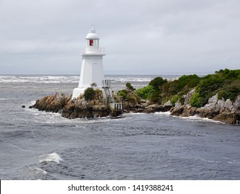 Hells Gates Lighthouse, close view with grey overcast weather, rough seas, Macquarie Harbour, Tasmania, Australia