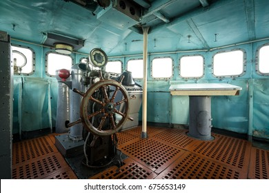 The helm and wheel in a boat cabin or war room with battle stations and instruments, consoles of old Battleship in World War 2