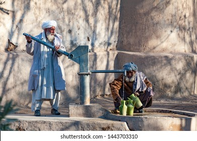 Helmand, Afghanistan - January 2011: Afghan men in Helmand collcet water from pump
