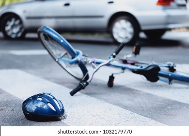 Helmet and bike lying on the road after a car hit a cyclist on a pedestrian crossing
