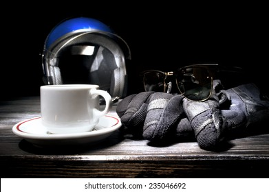 Helmet gloves and cup of coffee on table