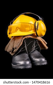 Helmet, gloves and scoop on a dark workbench. Safety and hygiene accessories for construction workers. Black background.