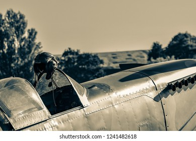 Helmet hanging from the cock[it window frame of a historic fighter. Sepia image of a classic warbird.
