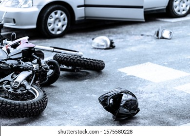 Helmet and motorcycle on the street after car crash