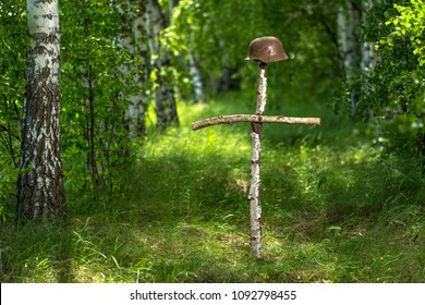 Helmet on the birch cross. The grave of an unknown German soldier in the forest. Imitation. WW2 recovery.