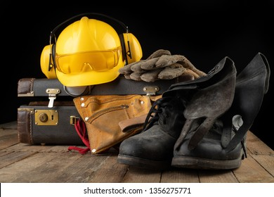 Helmet shoes and gloves on a travel suitcase. Working clothes prepared for traveling on a work table. Dark background.