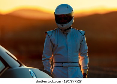 A Helmet Wearing Race Car Driver In The Early Morning Sun Looking At His Car Before Starting