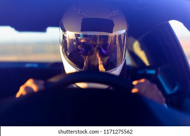 A Helmeted Race Car Driver At The Wheel