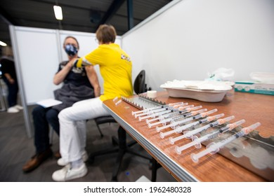 Helmond, Netherlands - April 24 2021: A man wearing facemask gets the anti-Covid vaccine. New Corona Vaccination center opens in the Netherlands, providing that day BioNTech Pfizer jabs.