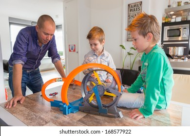 HELMOND, NETHERLANDS - OCTOBER 5, 2013: Children playing with a race track whilst the father is watching.