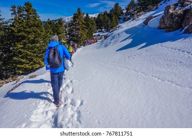 HELMOS MOUNT, GREECE - MARCH 2017: People Hiking from the ski resort of Aroania (also known as Helmos or Chelmos) Mountain heading to the Big Cave Monastery located above Zachlorou, Kalavryta, Greece.
