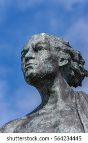 Helmsdale, Scotland - June 4, 2012: The Emigrant Statue at the south entrance of the town. Closeup of head of adult male. Blue sky, bronze with green spots.