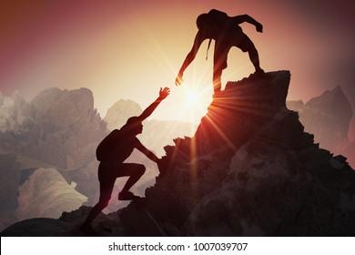 Hilfs- und Unterstützungskonzept. Silhouetten von zwei Menschen klettern auf den Berg und helfen.