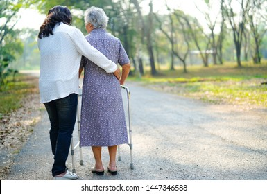 Help and care Asian senior or elderly old lady woman use walker with strong health while walking at park in happy fresh holiday.