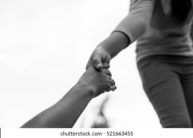 Help Concept Young girl Hands reaching out to help old woman in black and white