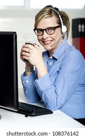 Help desk executive drinking coffee at work and looking at camera