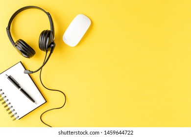 Help desk headset with notebook, pen and mouse on yellow desktop. Call center concept