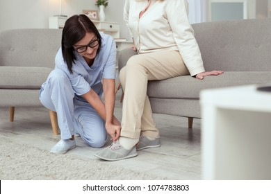 Help to dress. Elder woman posing on sofa while experienced caregiver putting on slippers