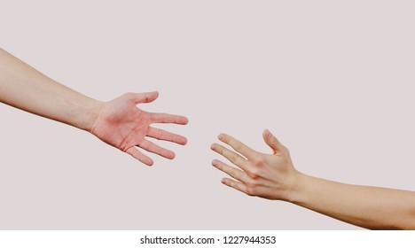 Help and help each other, reaching out for a helping hand. The hand is trying to grab the other hand. View of two hands on a bright gray background. Indifference to harm.