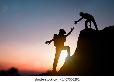 help and improve concept, silhouette people helping other hiker climbing rock and mountain