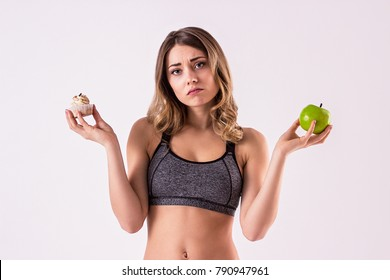 Help me to choose. Portrait of dissapointed sports woman deciding to choose healthy or unhealthy food while isolated on white background. Fitness girl with apple in one hand and cake in another