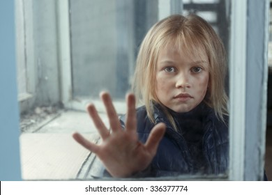 Help me. Little poor miserable girl  standing near window and begging for help while  holding her hand on glass