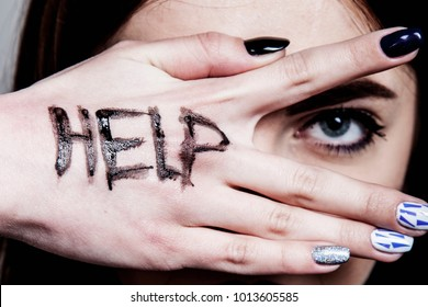 Help me! Woman's cries for help with painted inscription on her hand. (Fear, pain, danger, body language, gestures, psychology concept)
