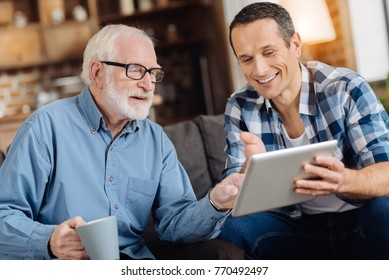 Help needed. Pleasant senior man sitting on the sofa next to his son and pointing at the tablet, asking his son to explain how to use the tablet