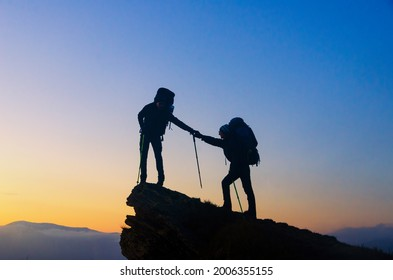 Help to reach the top. One hiker helps anothe to reach the summit. Coaching and friendly help concept