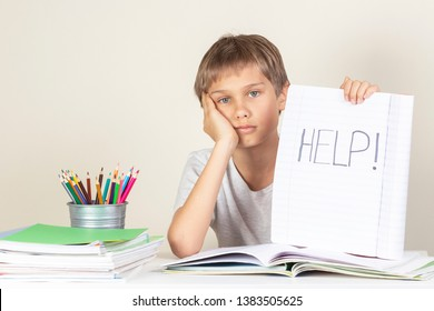 Help sign. Sad tired unhappy child doing homework and holding notebook with word Help