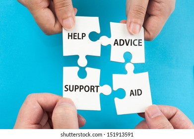 Help, support, aid and advice concept with two hands holding jigsaw puzzle pieces and putting them together